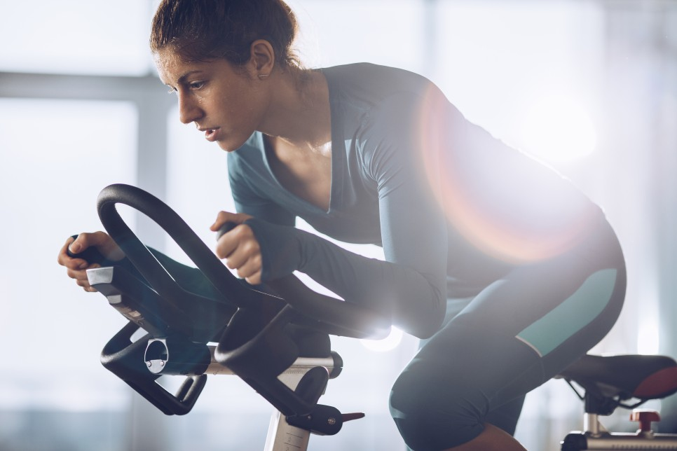 Athletic woman cycling on exercise bike during sports training in a gym.