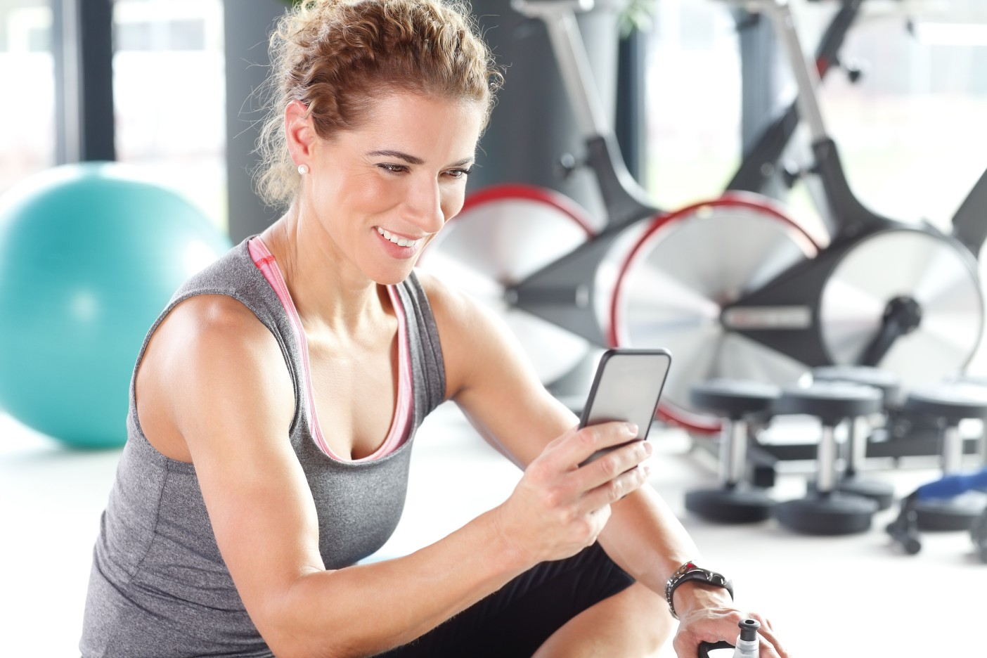 Portrait of personal trainer woman sitting at gym after fitness workout and checking sport app in her smartphone.